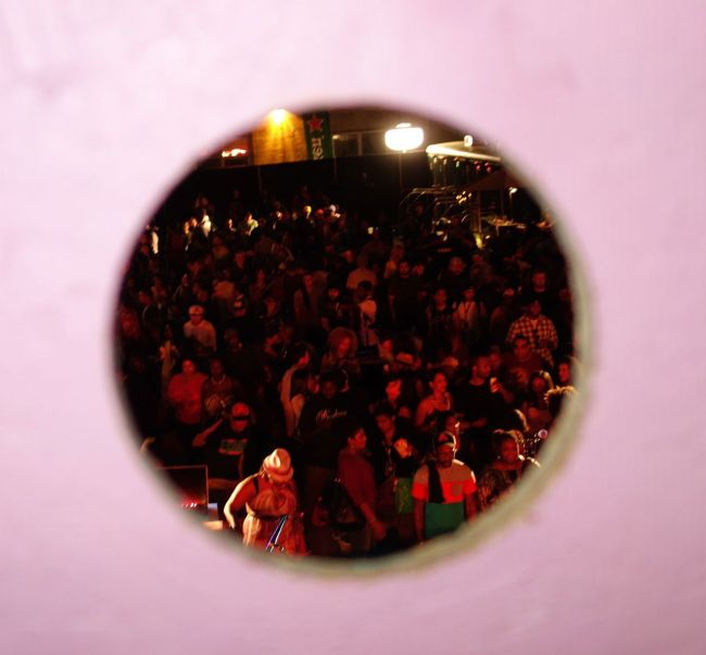 A view of a party down below through a hole in an art piece