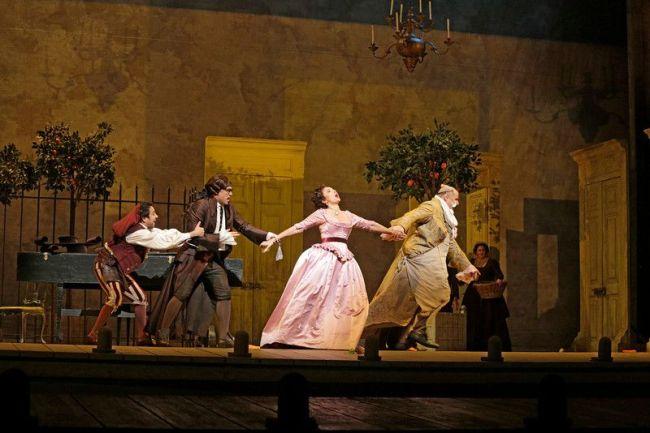 """A scene from Rossini's """"Il Barbiere di Siviglia,"""" with Isabel Leonard (center) as Rosina. Photo: Ken Howard/Metropolitan Oper"""